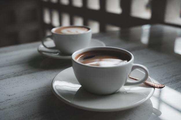 Duas xícaras brancas de café quente em cima da mesa