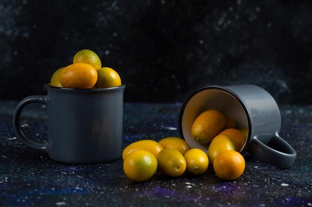 Duas xícaras cheias com kumquats frescos