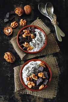 Duas xícaras com iogurte com sementes de chia, nozes e chocolate amargo. café da manhã ou sobremesa para dois. comida saudável.