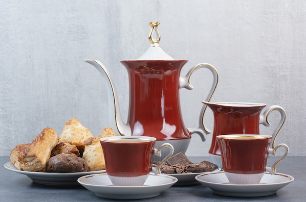 Duas xícaras de café aroma com bolos na mesa cinza.
