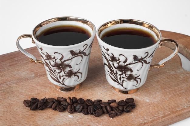 Duas xícaras de café brancas com grãos de café em uma placa arborizada.