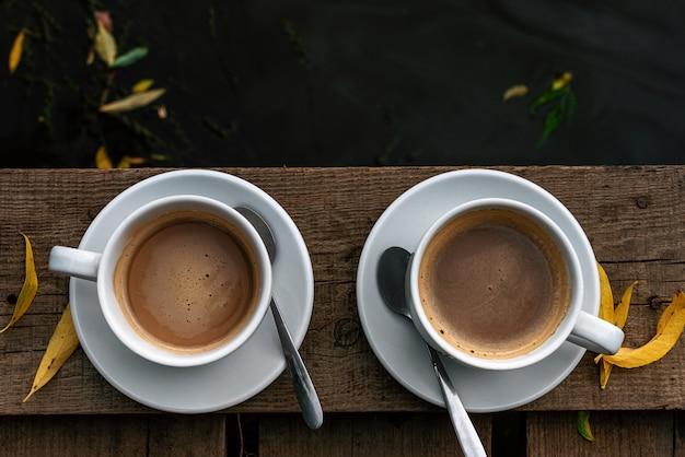 Duas xícaras de café brancas com leite em um piso de madeira sobre o rio