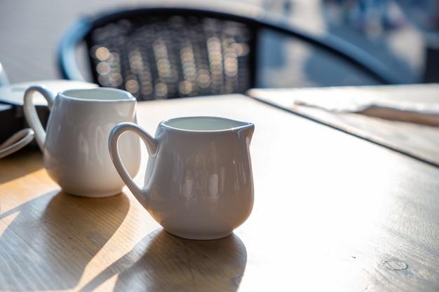 Duas xícaras de café brancas sobre uma mesa de café ao ar livre.