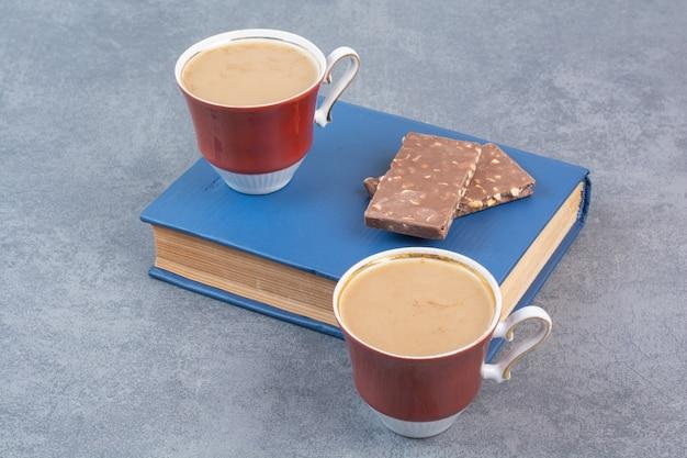 Duas xícaras de café com chocolates no livro.