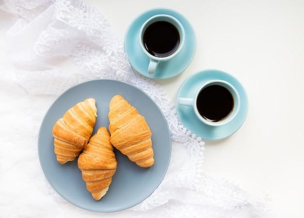 Duas xícaras de café com croissants no fundo de atacadores, close-up