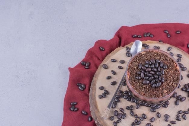 Duas xícaras de café com grãos de chocolate em uma travessa de madeira