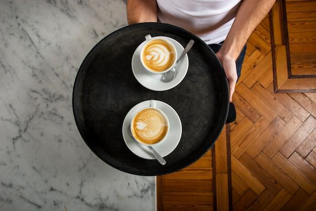 Duas xícaras de café com latte art na bandeja