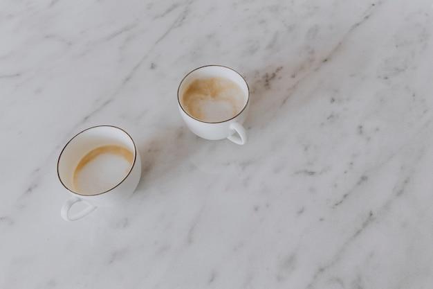 Duas xícaras de café com leite em uma mesa de mármore
