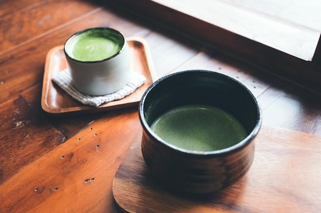Duas xícaras de café com leite matcha quente no chão de madeira