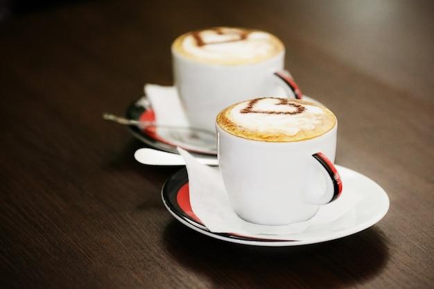 Duas xícaras de café com padrão de coração em um copos brancos na mesa de madeira