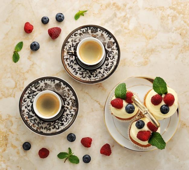 Duas xícaras de café e bolos com framboesas e mirtilos