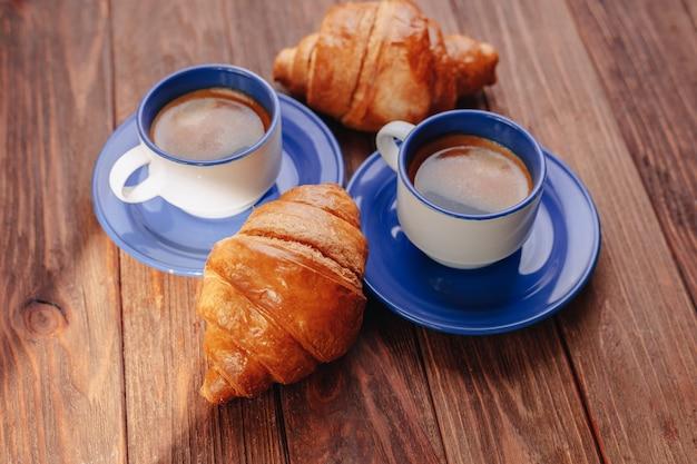 Duas xícaras de café e croissants em um fundo de madeira, boa luz, atmosfera de manhã