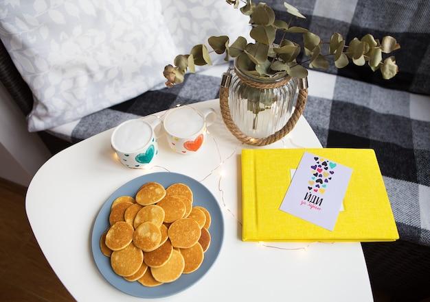 Duas xícaras de café e deliciosas panquecas estão sobre a mesa, álbum de fotos amarelo