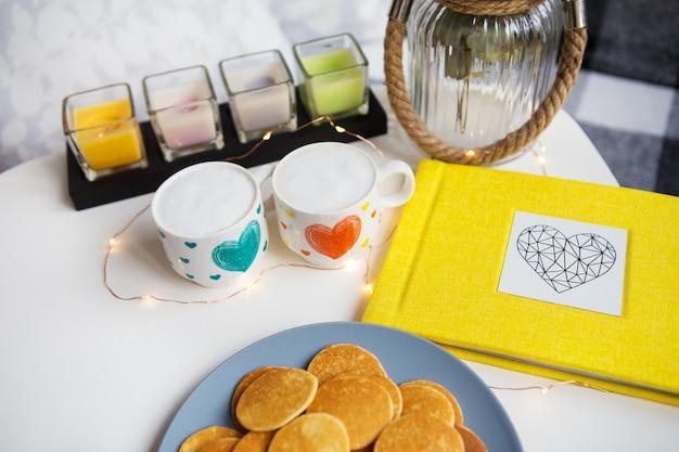 Duas xícaras de café e deliciosos punkcakes em cima da mesa, álbum de fotos amarelo, close-up