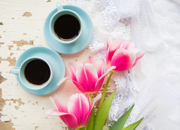 Duas xícaras de café e tulipas cor de rosa em uma mesa velha