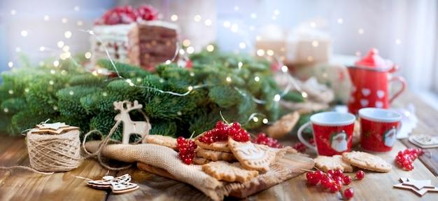 Duas xícaras de café e uma cafeteira, um bolo com frutas e biscoitos, presentes, perto de uma árvore de natal em uma mesa de aldeia perto da janela