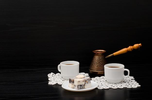 Duas xícaras de café em guardanapos brancos, panelas e doces em um fundo preto