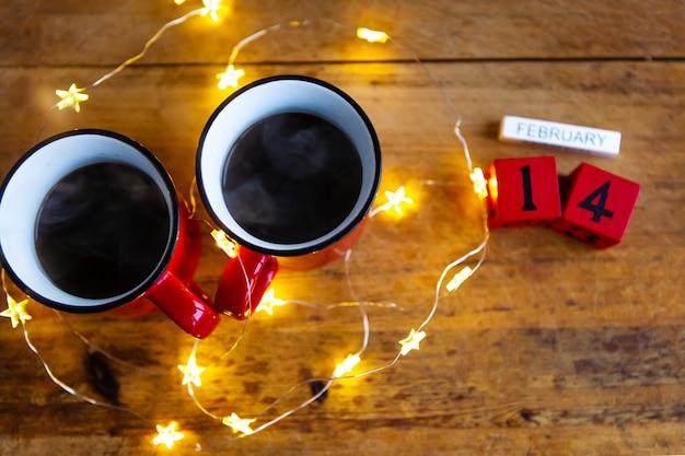 Duas xícaras de café em xícaras vermelhas em uma parede de guirlandas. café da manhã no dia dos namorados. conceito de amor.