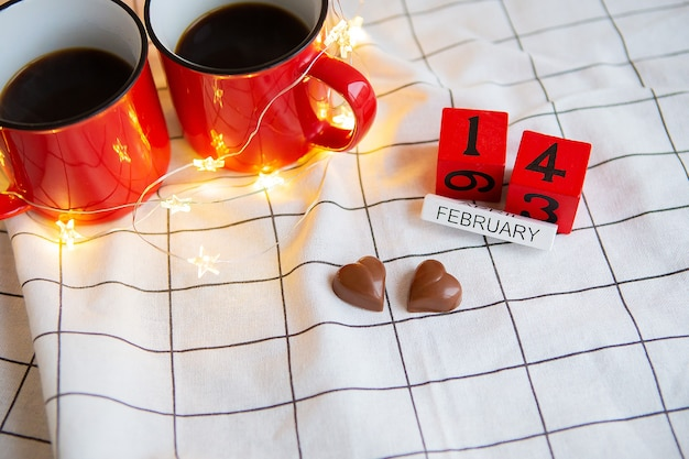 Duas xícaras de café em xícaras vermelhas sobre uma mesa com corações de chocolate. dia dos namorados surpresa de manhã.