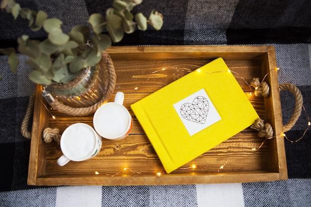 Duas xícaras de café estão em uma bandeja de madeira e um álbum de fotos amarelo