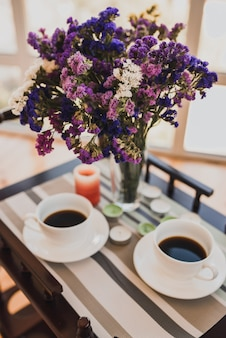 Duas xícaras de café estão em uma pequena mesa de vidro ao lado de um buquê de flores rosa roxas vibrantes em um vaso