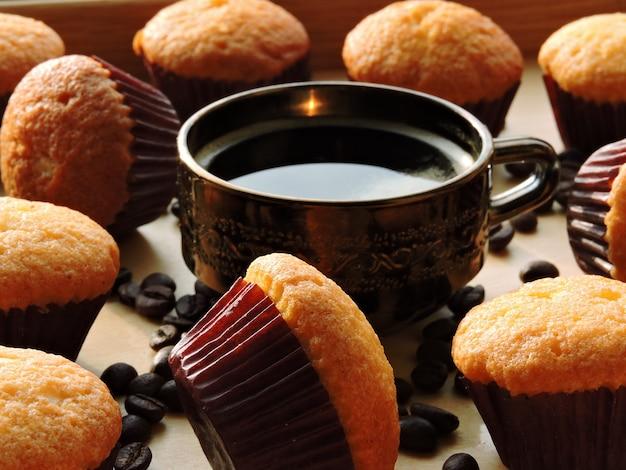 Duas xícaras de café expresso, mini muffins, grãos de café.