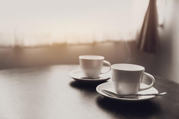 Duas xícaras de café na mesa perto do conceito de amor romântico de manhã de windows