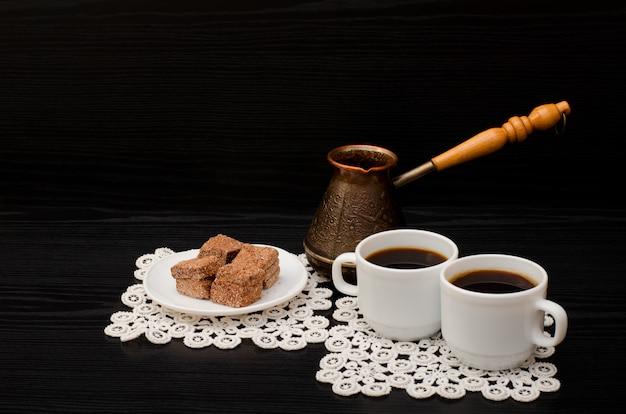 Duas xícaras de café nos guardanapos de renda, panelas e sobremesa turca de chocolate em um fundo preto