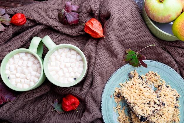 Duas xícaras de café ou chocolate quente com marshmallow perto de cobertor de malha,