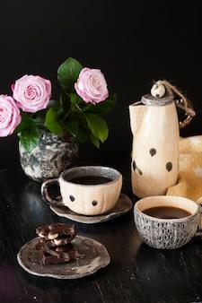 Duas xícaras de café preto, chocolate preto, um bule de chá amarelo e um vaso com rosas em uma superfície escura