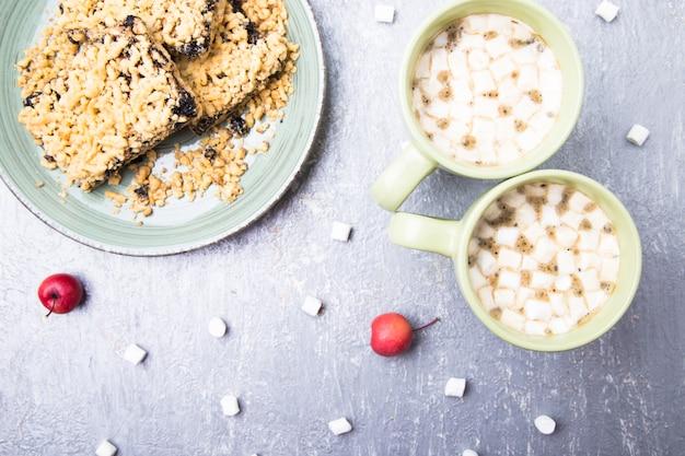 Duas xícaras de café quente ou chocolate e bolo ralado com marshmallow,