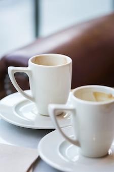 Duas xícaras de café vazias sobre uma mesa em um café. composição de estilo de vida com luz natural