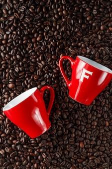 Duas xícaras de café vermelhas na mesa de grãos de café recém-torrados