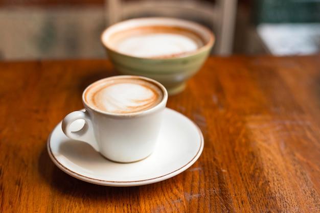 Duas xícaras de cappuccino com latte art na mesa de madeira. conceito de pequeno-almoço fácil. copos de cerâmica pequenos e grandes