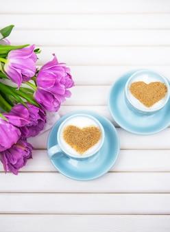 Duas xícaras de cappuccino com um símbolo em forma de coração e tulipas roxas em um fundo de madeira, close-up