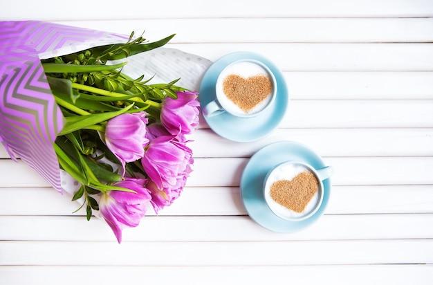 Duas xícaras de cappuccino com um símbolo em forma de coração e tulipas roxas em um fundo de madeira