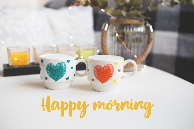 Duas xícaras de cappuccino em um fundo de velas - inscrição feliz manhã