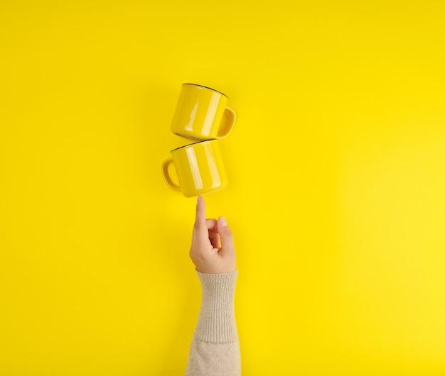 Duas xícaras de cerâmica amarelas são apoiadas por uma mão feminina