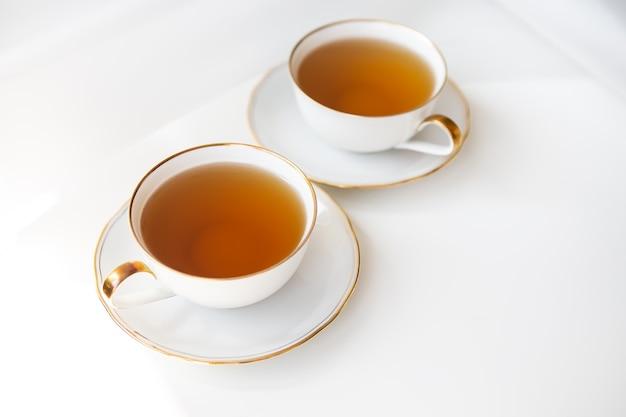 Duas xícaras de chá. chá preto em uma bela xícara de porcelana branca com um corte dourado. lindo sol. conceito de cerimônia do chá.