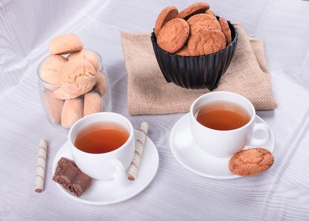 Duas xícaras de chá com biscoito e chocolate