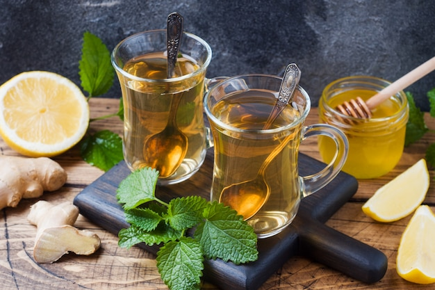 Duas xícaras de chá de ervas naturais gengibre hortelã limão e mel numa superfície de madeira.