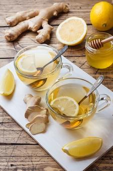 Duas xícaras de chá de ervas naturais gengibre limão e mel numa superfície de madeira.