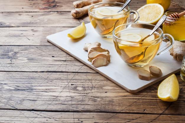 Duas xícaras de chá de ervas natural, gengibre, limão e mel copie o espaço