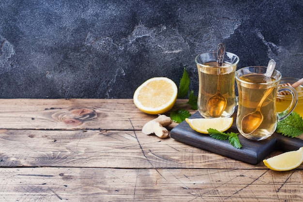 Duas xícaras de chá de ervas natural, gengibre, limão, hortelã e mel