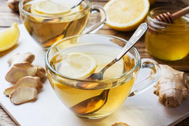 Duas xícaras de chá de gengibre natural limão limão e mel em um fundo de madeira.