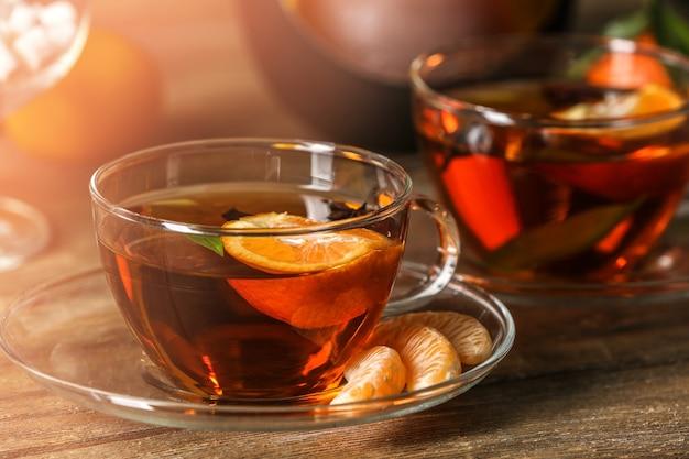 Duas xícaras de chá de tangerina em fundo de madeira