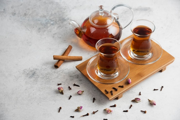 Duas xícaras de chá de vidro com paus de canela e rosas secas.