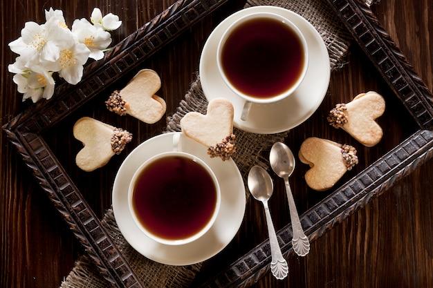 Duas xícaras de chá e biscoitos de forma de coração