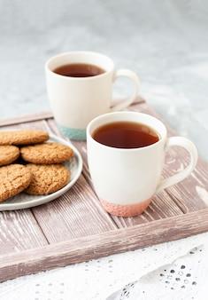 Duas xícaras de chá e um prato de biscoitos