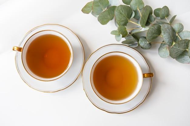 Duas xícaras de chá estão sobre a mesa, um galho de eucalipto. chá preto em uma bela xícara de porcelana branca com um corte dourado.